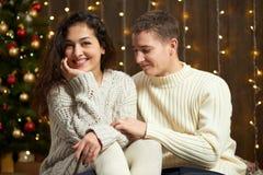 在圣诞灯和装饰的夫妇,穿戴在白,女孩和人,在黑暗的木背景,冬天holida的杉树 免版税库存图片
