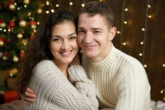在圣诞灯和装饰的夫妇,穿戴在白,女孩和人,在黑暗的木背景,冬天holida的杉树 库存照片