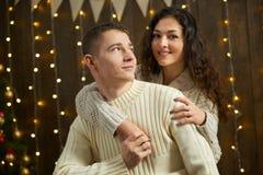 在圣诞灯和装饰的夫妇,穿戴在白,女孩和人,在黑暗的木背景,冬天holida的杉树 图库摄影