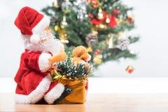 在圣诞老人和圣诞树旁边 图库摄影