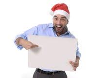 在圣诞老人圣诞节帽子指向空白的广告牌的英俊的商人 库存照片