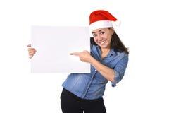 在圣诞老人圣诞节帽子指向空白的广告牌的年轻甜拉丁妇女 图库摄影