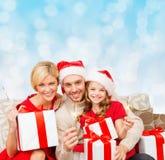在圣诞老人帮手帽子的愉快的家庭有礼物盒的 免版税图库摄影
