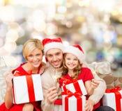 在圣诞老人帮手帽子的愉快的家庭有礼物盒的 免版税库存照片
