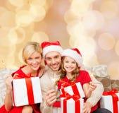 在圣诞老人帮手帽子的愉快的家庭有礼物盒的 免版税库存图片