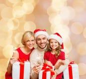 在圣诞老人帮手帽子的愉快的家庭有礼物盒的 库存照片