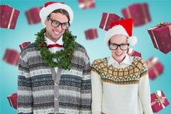 在圣诞老人帽子、眼镜和圣诞节装饰的愉快的夫妇 免版税库存照片