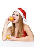 在圣诞老人帽子吃普通话的妇女 图库摄影