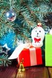 在圣诞老人帽子和圣诞节礼物的一个玩具狗在具球果分支背景  图库摄影