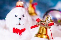在圣诞老人帽子和圣诞节礼物的一个玩具狗在具球果分支背景  免版税库存照片