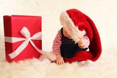 在圣诞老人帽子和礼物之外的婴孩 库存照片