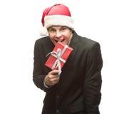 在圣诞老人帽子尖酸的红色礼物的滑稽的商人 库存图片