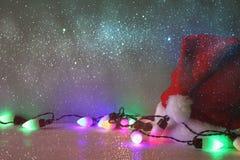 在圣诞老人帽子旁边的五颜六色的诗歌选光 闪烁覆盖物 免版税库存照片