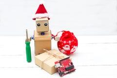 在圣诞老人帽子的一个机器人拿着一个螺丝刀和圣诞节玩具  库存照片