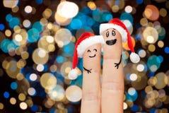 在圣诞老人帽子的两个手指在圣诞灯 库存照片