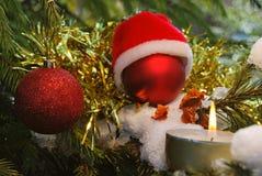 在圣诞老人帽子的圣诞节红色球有灼烧的蜡烛的 图库摄影