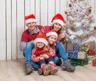 在圣诞老人帽子的大家庭在圣诞树附近 免版税库存图片