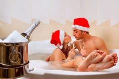 在圣诞老人帽子的夫妇享受浴 免版税库存照片
