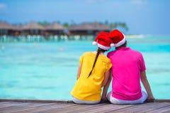 在圣诞老人帽子的夫妇在一个热带海滩在 库存图片