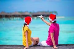 在圣诞老人帽子的夫妇在一个热带海滩在 库存照片