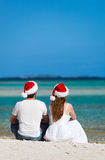 在圣诞老人帽子的夫妇在海滩 免版税库存图片