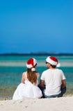 在圣诞老人帽子的夫妇在海滩 库存图片