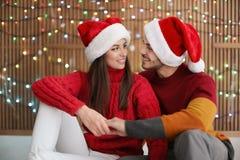 在圣诞老人帽子的夫妇在被弄脏的光背景 庆祝庆祝圣诞节女儿帽子母亲圣诞老人佩带 免版税库存图片