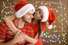 在圣诞老人帽子的夫妇在被弄脏的光背景 庆祝庆祝圣诞节女儿帽子母亲圣诞老人佩带 免版税库存照片