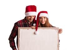 在圣诞老人帽子的夫妇有横幅的 免版税库存照片
