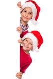 在圣诞老人帽子的孩子有whiteboard的 库存照片