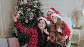 在圣诞老人帽子的家庭在圣诞树作为selfie附近 股票视频