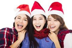 在圣诞老人帽子的少妇小组 免版税库存照片
