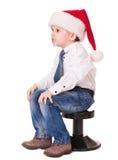 在圣诞老人帽子的恼怒的孩子在椅子 库存图片