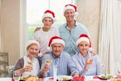 在圣诞老人帽子的愉快的大家庭敬酒在照相机的 免版税库存图片