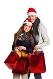 在圣诞老人帽子的愉快的夫妇有礼物的 免版税图库摄影