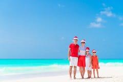 在圣诞老人帽子的愉快的家庭在热带圣诞节假期时 免版税库存图片