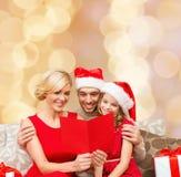 在圣诞老人帽子的愉快的家庭有贺卡的 免版税库存照片