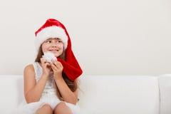 在圣诞老人帽子的愉快的小女孩孩子 圣诞节 免版税库存照片
