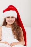 在圣诞老人帽子的愉快的小女孩孩子 圣诞节 免版税库存图片