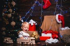 在圣诞老人帽子的愉快的小孩子有当前的有圣诞节 逗人喜爱的小孩装饰圣诞树户内 图库摄影