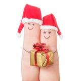 在圣诞老人帽子的手指面孔有礼物盒的 愉快的夫妇 免版税库存图片