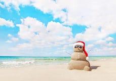 在圣诞老人帽子的桑迪雪人在海海滩 新年和圣诞节 库存图片