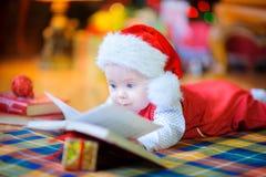 在圣诞老人帽子的滑稽的孩子 库存照片