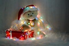 在圣诞老人帽子的玩具熊有礼物的 库存照片