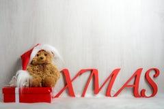 在圣诞老人帽子的玩具熊有礼物的 免版税库存图片