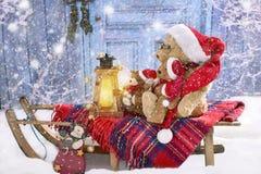在圣诞老人帽子的玩具熊sledding在多雪的晚上 免版税库存照片