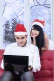 在圣诞老人帽子的西班牙夫妇使用膝上型计算机 库存图片