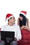 在圣诞老人帽子的年轻夫妇使用膝上型计算机 图库摄影