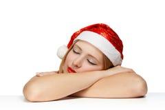 在圣诞老人帽子睡觉在桌上的美丽的少妇我 库存图片