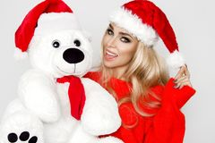 在圣诞老人帽子穿戴的美好的性感的白肤金发的女性模型拥抱在一个红色盖帽Christm的一个白色玩具熊 图库摄影
